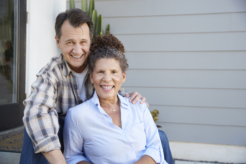 Portrait Of Senior Couple Sitting Outside Grey Clapboard House